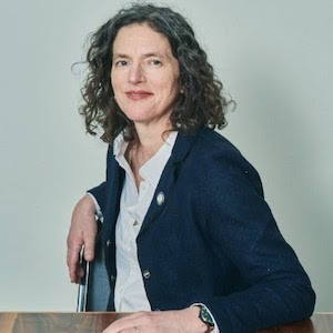 image of smiling white woman with dark curly hair sitting at a table wearing dark blue blazer and white button up shirt