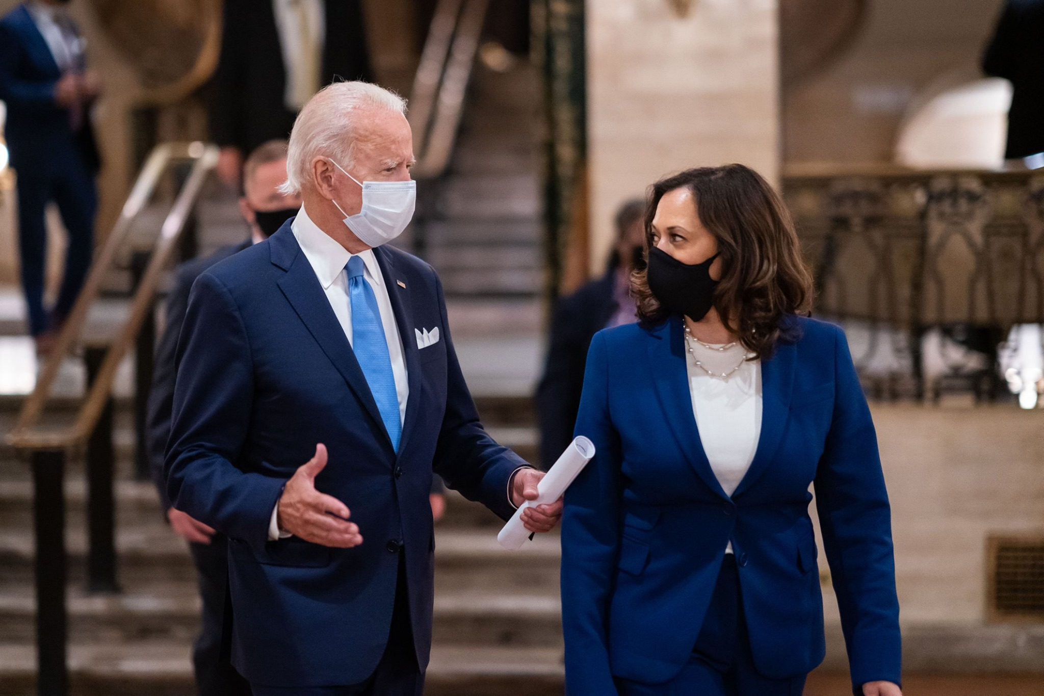 white man with grey hair navy suit and blue tie wearing a mask talking to black woman with shoulder length brown hair wearing a black mask with a navy suit jacket and white shirt